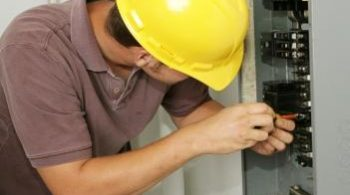 An electrician working on an electrical breaker panel.  Model is an actual electrician - all work is being performed according to industry codes and safety standards.